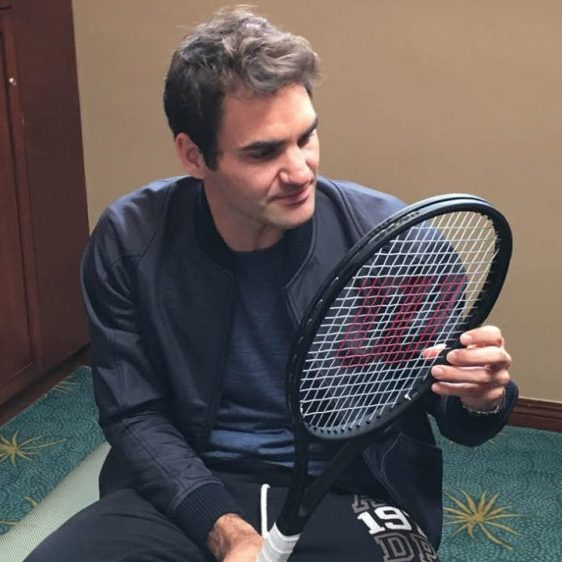 Roger Federer looking at his strings